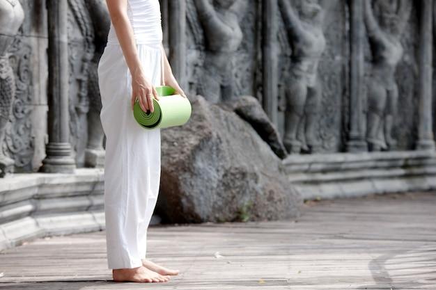 Frau, die yoga im verlassenen tempel auf hölzerner plattform praktiziert
