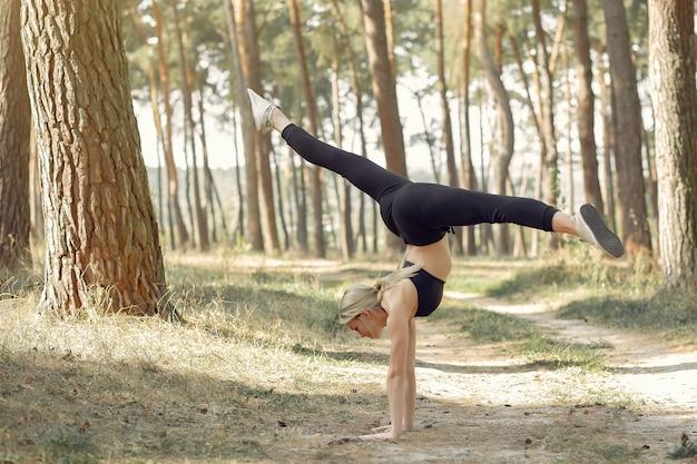 Frau, die yoga in einem sommerwald tut