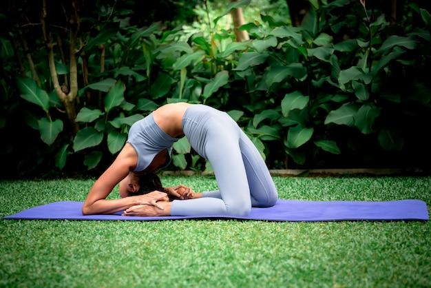 Frau, die yoga in einer eleganten haltung im grünen park tut