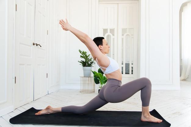 Frau, die yoga in ihrem minimalen weißen haushintergrund praktiziert