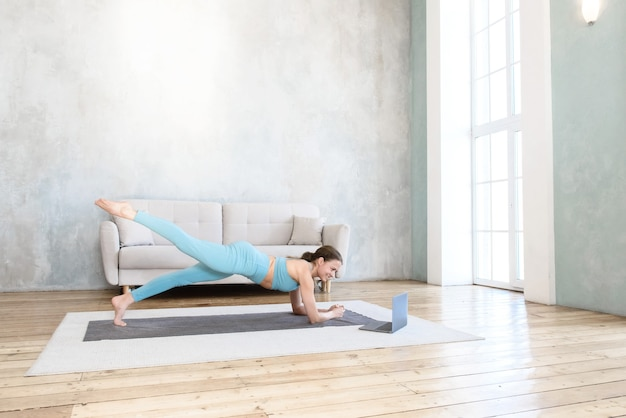 Frau, die yoga macht, das online mit laptop von zu hause aus streckt