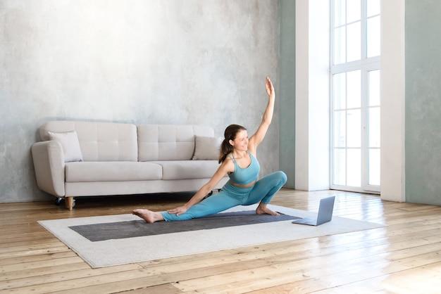Frau, die yoga macht, die zu hause das video auf dem laptop ausdehnt