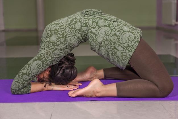 Frau, die yoga macht, erstreckt sich im fitnessstudio.