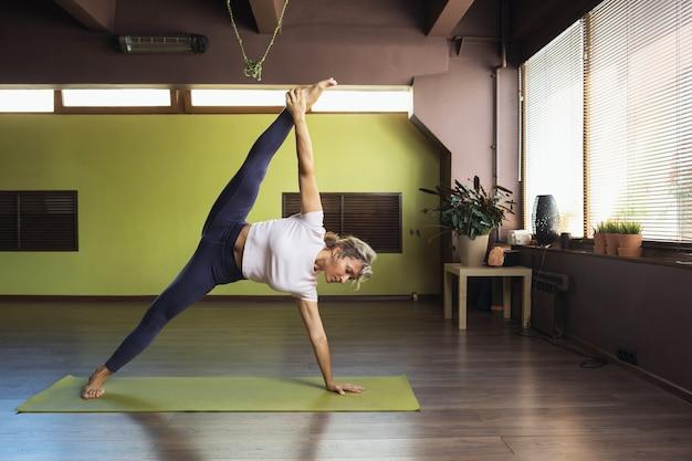 Frau, die yoga macht, führt im studio die übung vasishthasana durch