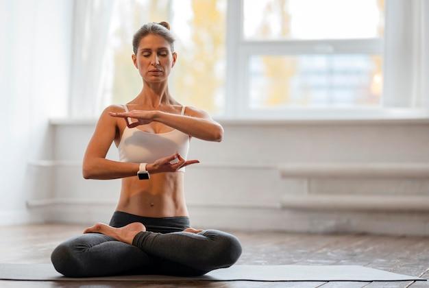 Frau, die yoga mit kopienraum auf matte zu hause ausübt