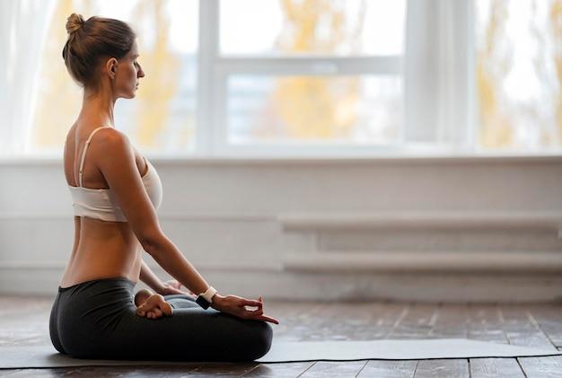 Frau, die yoga mit kopienraum zu hause ausübt