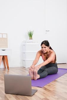 Frau, die yoga mit laptop tut