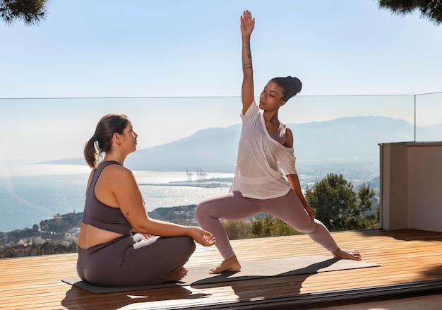 Frau, die yoga mit lehrer auf matte tut