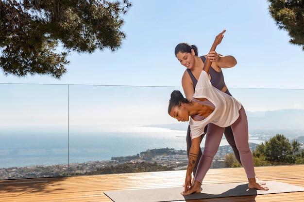 Frau, die yoga mit lehrer macht
