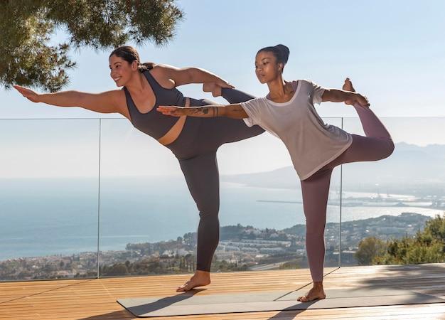 Frau, die yoga mit lehrer voll erschossen macht