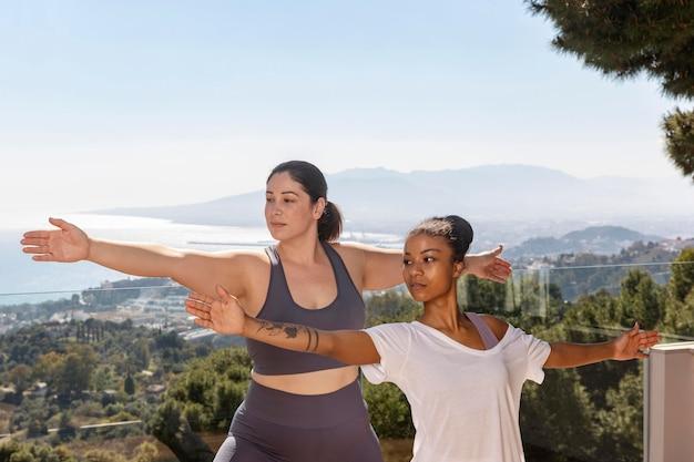 Frau, die yoga mit mittlerem schuss des lehrers tut