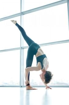 Frau, die yoga neben fenster macht