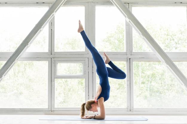 Frau, die yoga oder pilates übung und handstandhaltung tut.