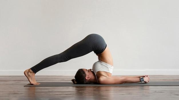 Frau, die yoga-positionen zu hause ausübt