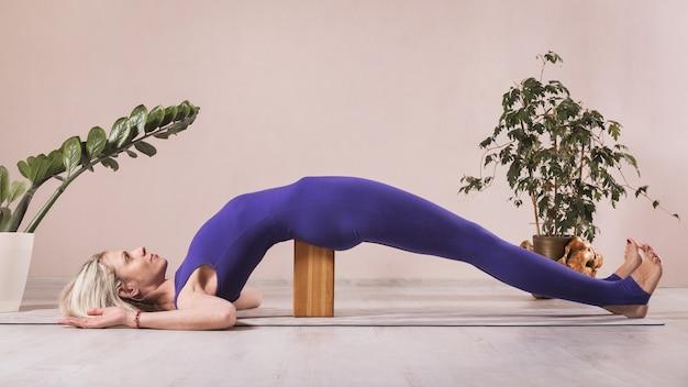 Frau, die yoga praktiziert, die seto bandha sarvangasana übung mit hölzernem yogablock macht, der auf einer matte im studio nahe der wand ausübt