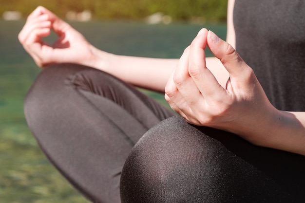 Frau, die yoga praktiziert oder in der nähe des sees über die natur meditiert