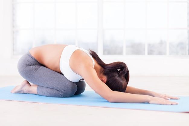Frau, die yoga praktiziert. seitenansicht der jungen frau, die sich auf der yogamatte ausdehnt