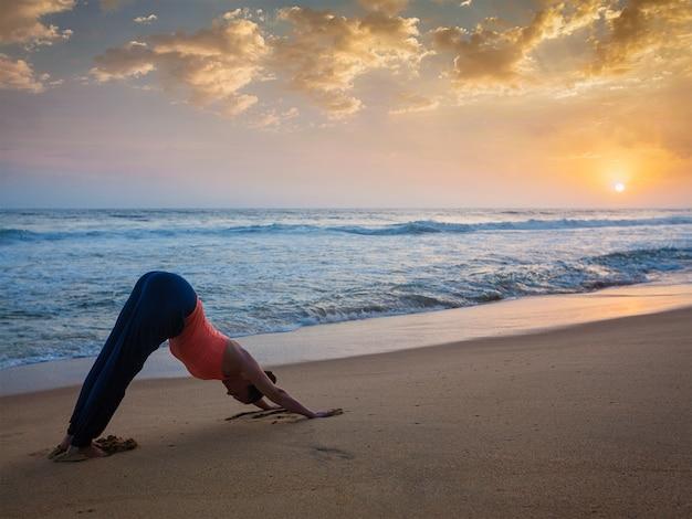 Frau, die yoga surya namaskar draußen am tropischen strand tut