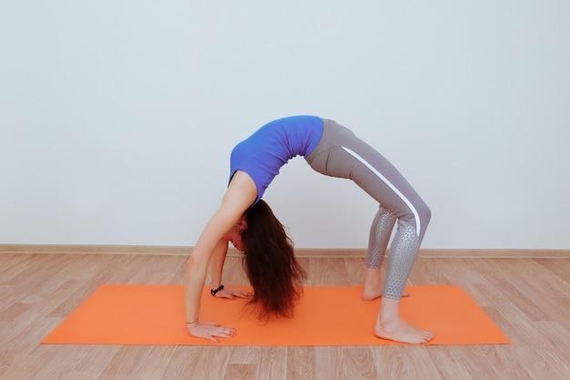 Frau, die yoga-übung auf orangefarbener matte macht und sich streckt.