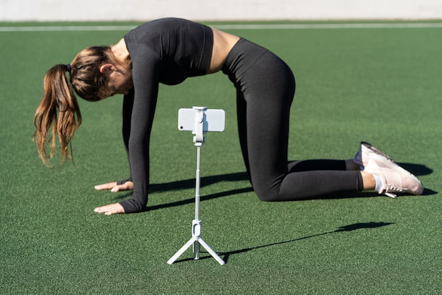 Frau, die yoga-übung namens katzenhaltung im freien tut