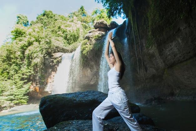 Frau, die yoga und meditation am wasserfall tut