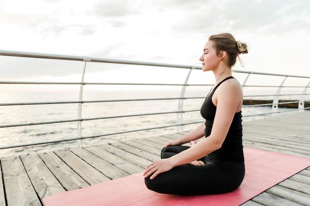 Frau, die yoga und meditation nahe dem meer auf sonnenaufgang tut