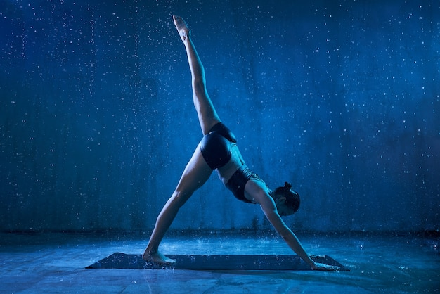 Frau, die yoga unter regen praktiziert