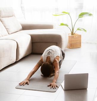 Frau, die yoga zu hause auf matte mit laptop auf dem boden tut