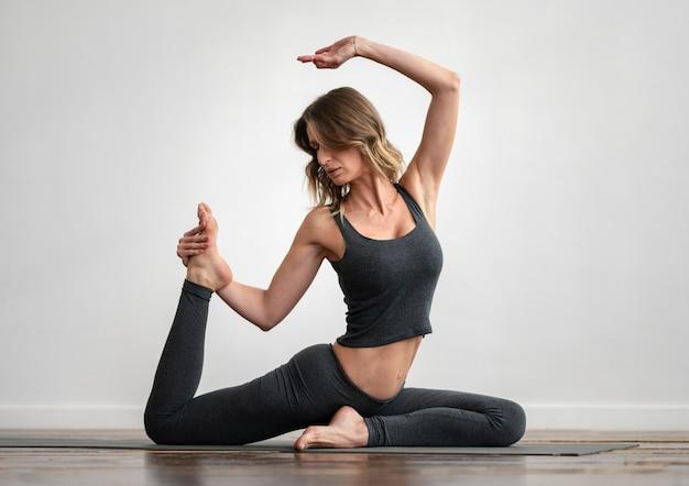 Frau, die yoga zu hause auf matte tut