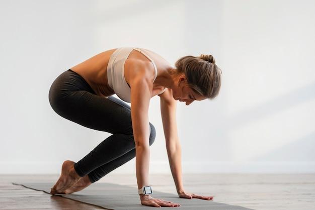 Frau, die yoga zu hause ausübt