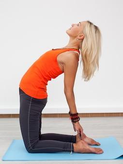 Frau, die yogatraining tut
