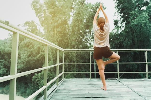 Frau, die yogaübung am morgen mit natürlichem hintergrund tut.