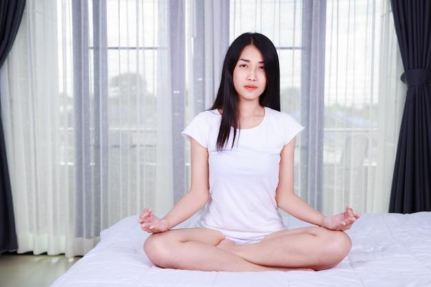 Frau, die yogaübung auf bett im schlafzimmer tut