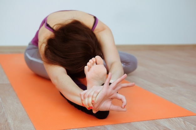 Frau, die yogaübung auf orange matte tut.