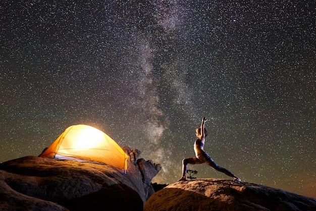 Frau, die yogaübungen auf berggipfel in der nacht tut