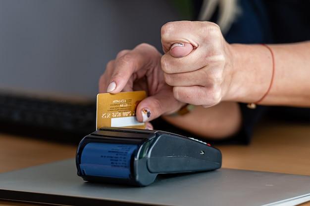 Frau, die zahlungskartenterminal benutzt, um online mit kreditkarte einzukaufen und zeigt eine feige mit seiner anderen hand