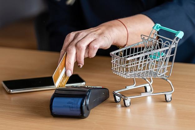 Frau, die zahlungskartenterminal verwendet, um online mit kreditkarte, kreditkartenleser, finanzkonzept einzukaufen