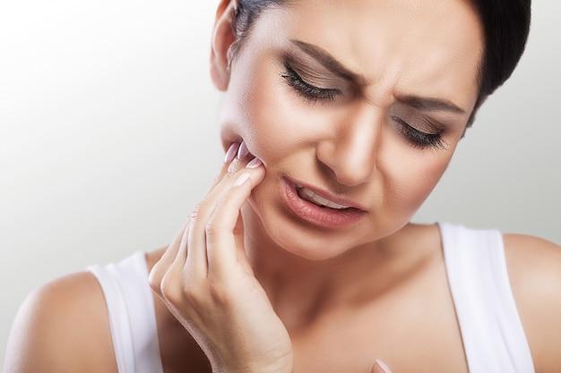 Frau, die zahnschmerzen glaubt
