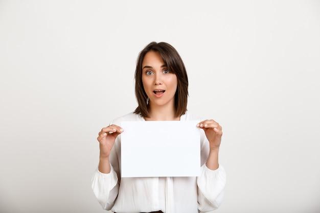 Frau, die zeichen auf weißem papier zeigt, machen ankündigung