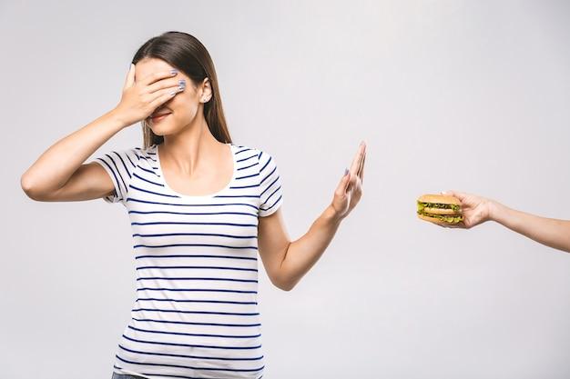 Frau, die zeichen nein tut, um junk-food abzulehnen