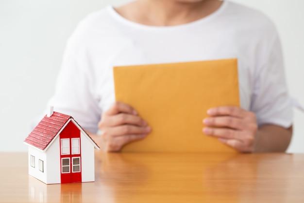 Frau, die zeichenvereinbarungsvertrag, versicherungshaus und immobilienkonzept hält