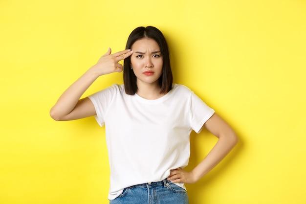 Frau, die zeigt, töte mich bitte, gestikuliere, schieße sich vor langeweile mit der fingerpistole in den kopf und stehe verärgert über gelb.
