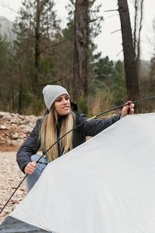 Frau, die zelt für camping vorbereitet