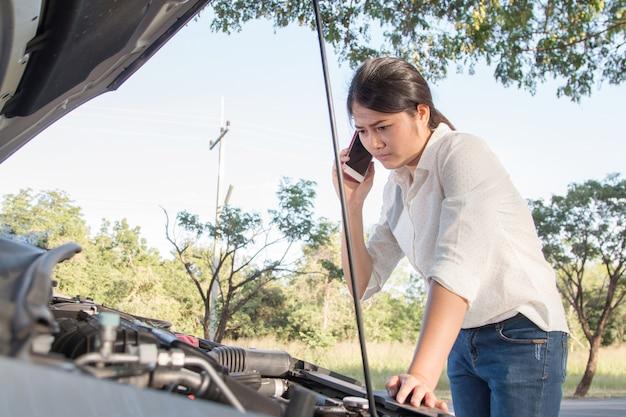 Frau, die zerbrochenen automotor auf straße betrachtet. haube öffnen und um hilfe auf ce bitten