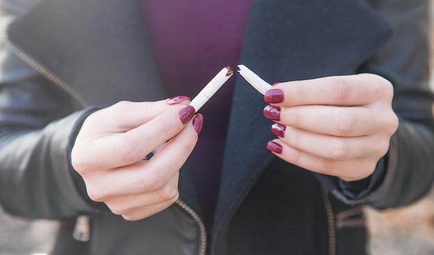 Frau, die zigarette bricht. mit dem rauchen aufhören