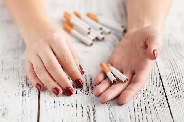 Frau, die zigarette über weißer oberfläche bricht