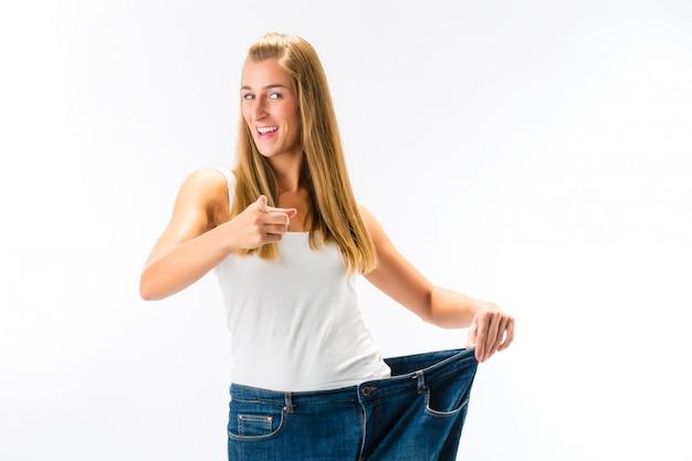 Frau, die zu große hosen steht und trägt, nachdem gewicht gelöst worden ist