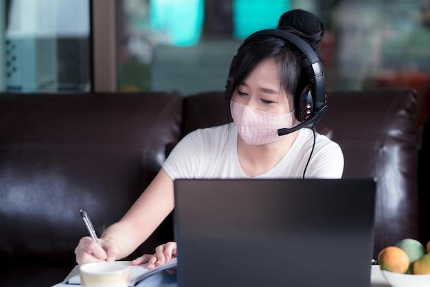 Frau, die zu hause am laptop mit gesichtsmaske zum schutz für schutz 2019 arbeitet - ncov, covid 19 oder coronavirus.wfh oder working from home-konzept.