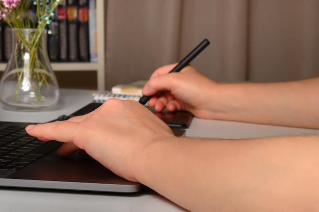 Frau, die zu hause an einem laptop und einem grafiktablett arbeitet