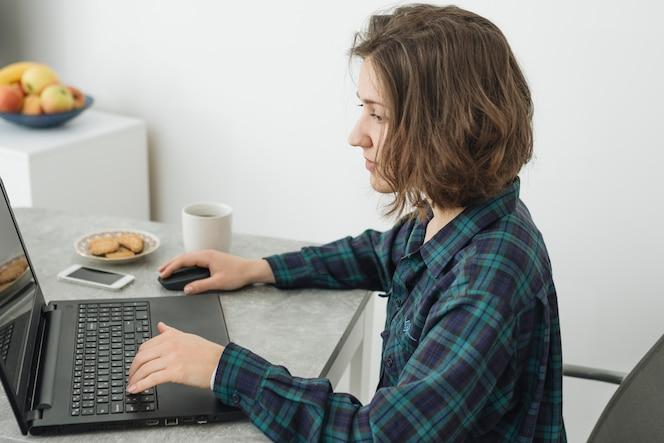 Frau, die zu hause an laptop arbeitet